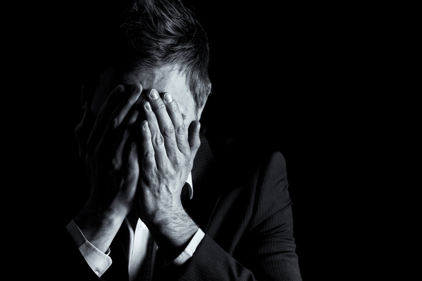 desperate office manager in dark suit covering his face