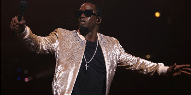 Diddy (Sean Combs) performing on stage while wearing sunglasses.