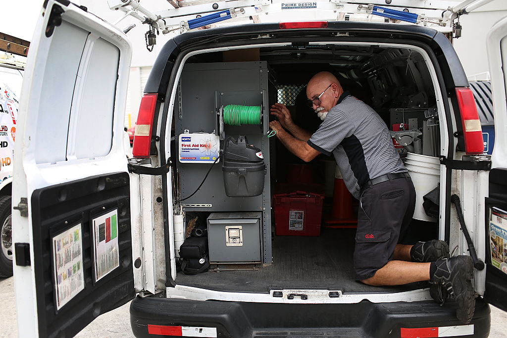 Alberto Rodriguez a Dish Network technician works around one of the company trucks on June 4, 2015
