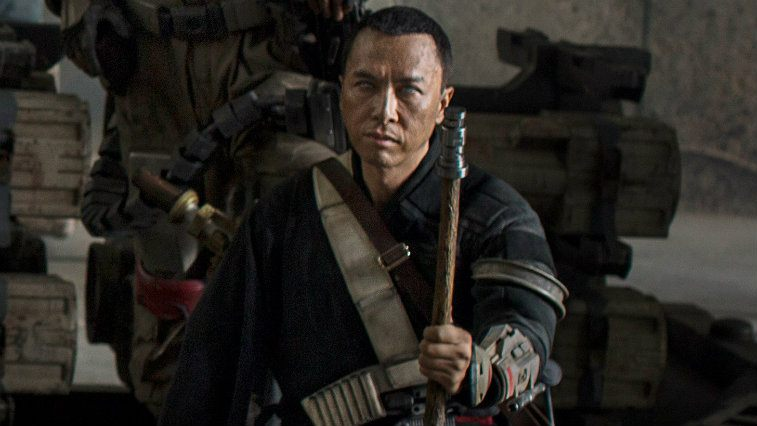Donnie Yen in Rogue One holding out his stick while in fighting gear