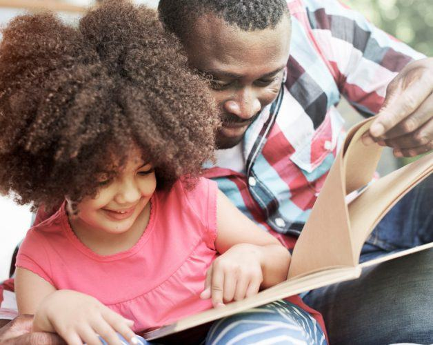 A father and daughter read a book and listen to Amazon Echo