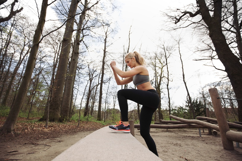 Fitness woman doing stepping up exercise in forest