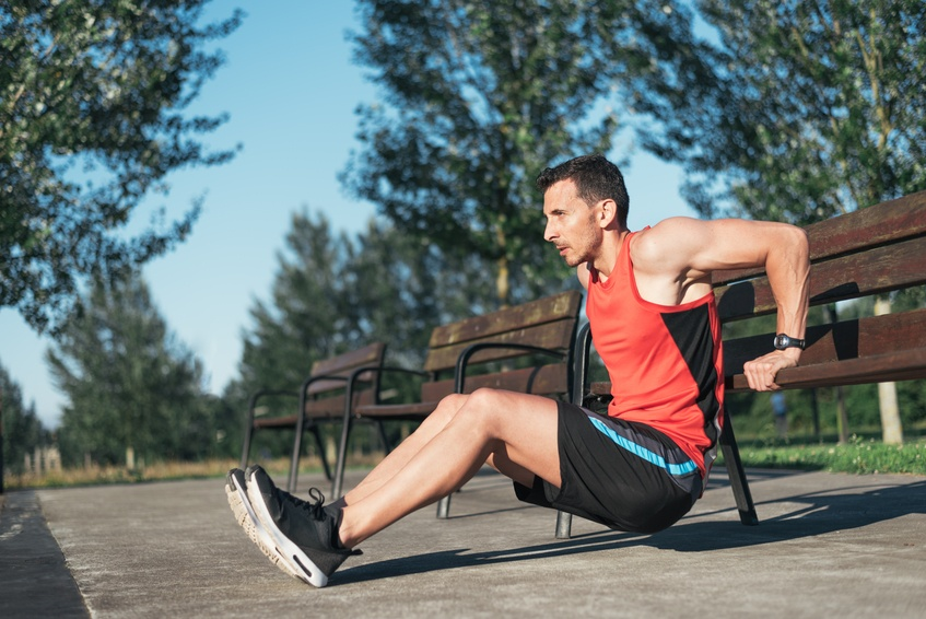 Fitness man doing bench triceps dips