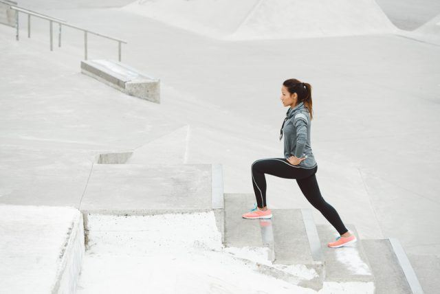 Woman practicing perform form doing stair lunges