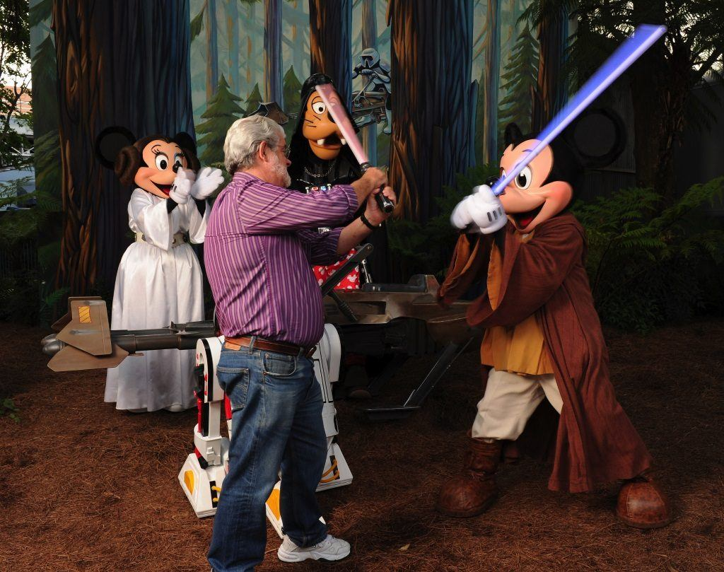 George Lucas has a playful lightsaber duel with Jedi Mickey Mouse