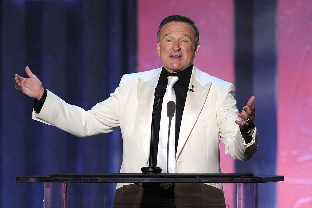 Robin Williams speaks onstage in a white suit
