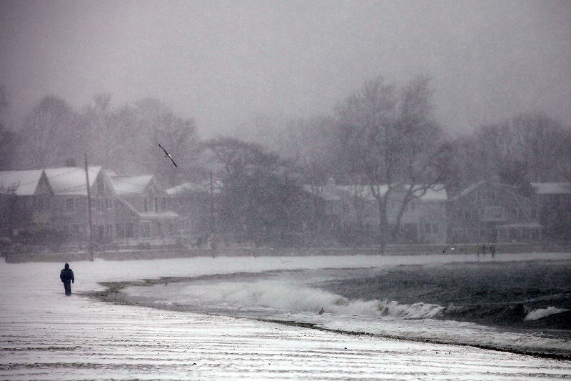 A man walks along a Connecticut beach through a snow storm