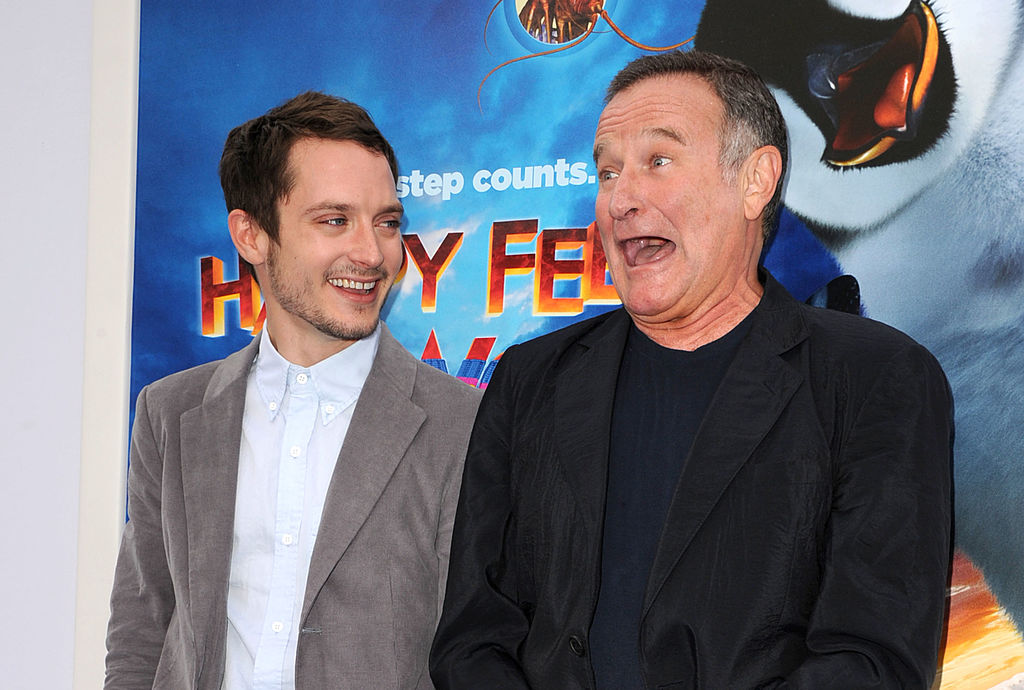 Elijah Wood and Robin WIlliams in front of a Happy Feet poster