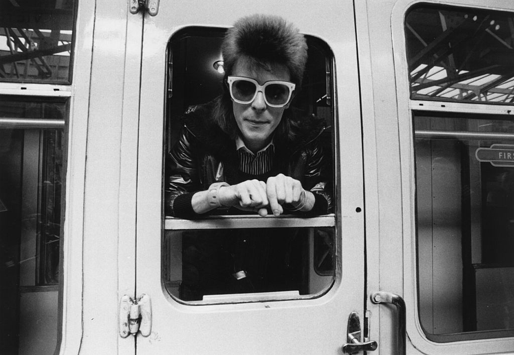 David Bowie at a photoshoot looking out of a train door with sunglasses on