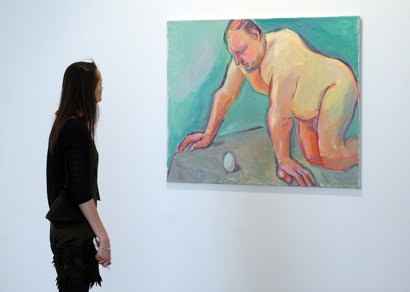 A woman looks at a painting in a Russian museum exploring body image issues