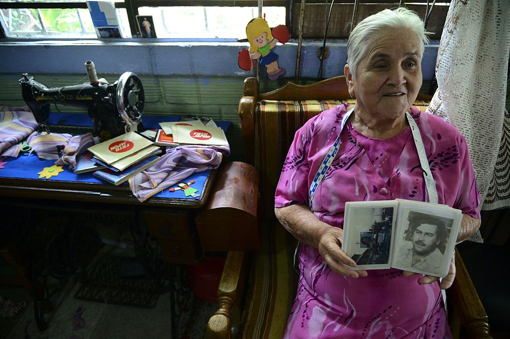 Irene Gaviria shows an album with pictures of late Colombian drug lord Pablo Escobar | RAUL ARBOLEDA/AFP/Getty Images)