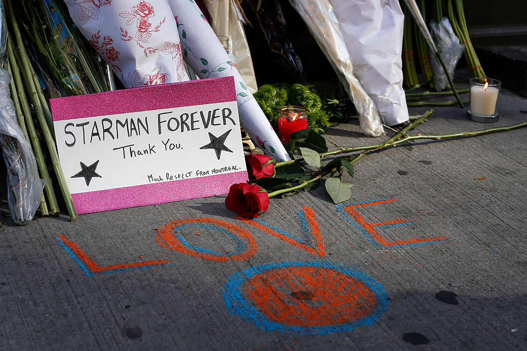 A memorial outside David Bowie's house with flowers and cards