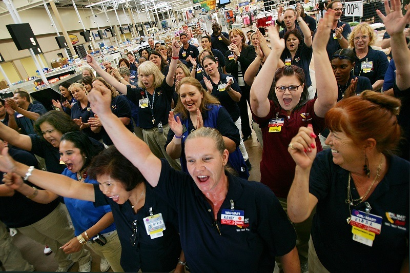 Employees give the Wal-Mart cheer during their daily staff meeting
