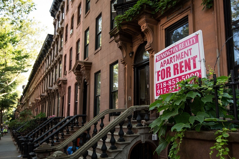 A sign advertises an apartment for rent along a row of brownstone townhouses