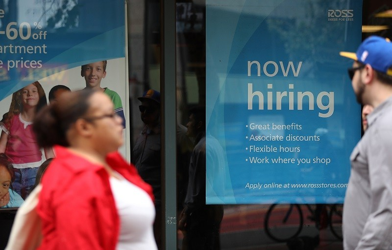 A 'now hiring' sign is posted outside of a store, advertising opportunities for employment