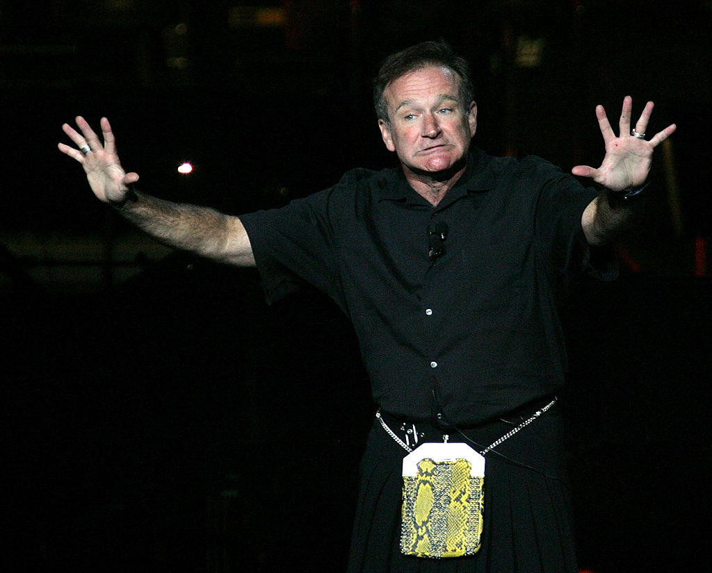 Robin Williams performs onstage with his hands up