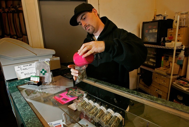 A budtender packages medical cannabis