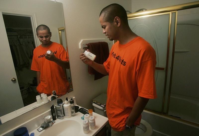 An Iraq War veteran inspects his mental health medications