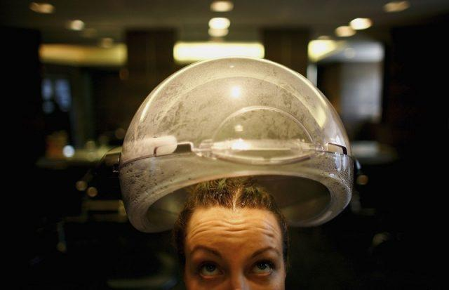 A Hari's salon employee has her hair steamed after application