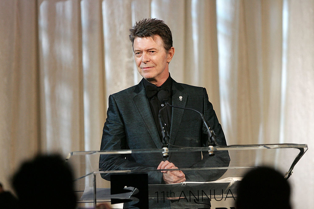 David Bowie speaks on-stage ub a black suit