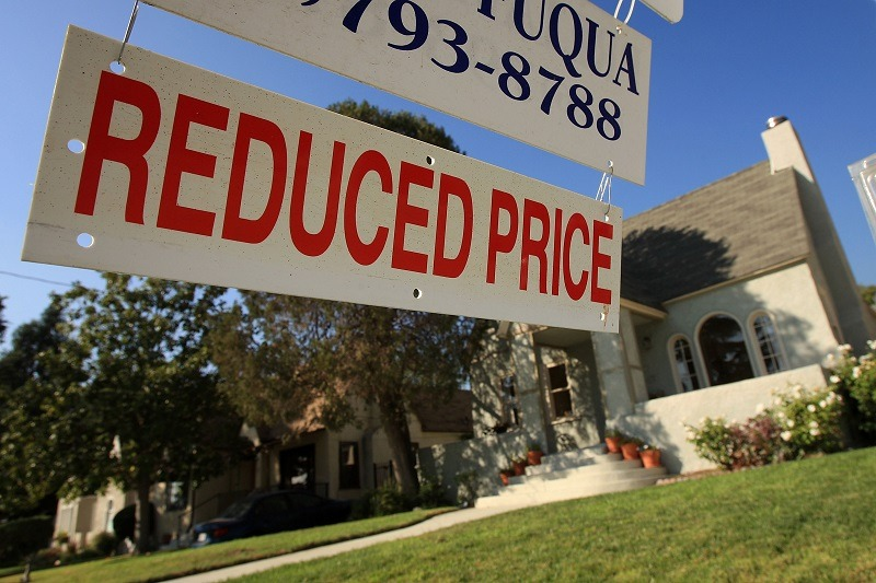 A realtor sign in an area where house prices and real estate values are dropping