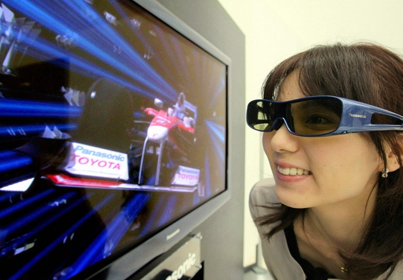 A woman views three-dimensional images through special glasses