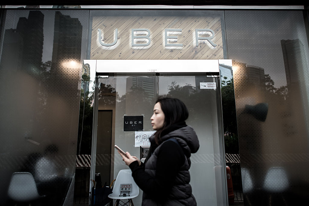 A woman walks past the Uber offices in Hong Kong