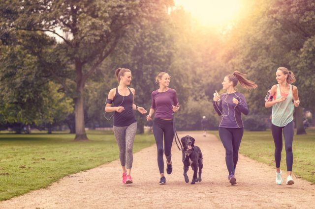 four women jogging with dog