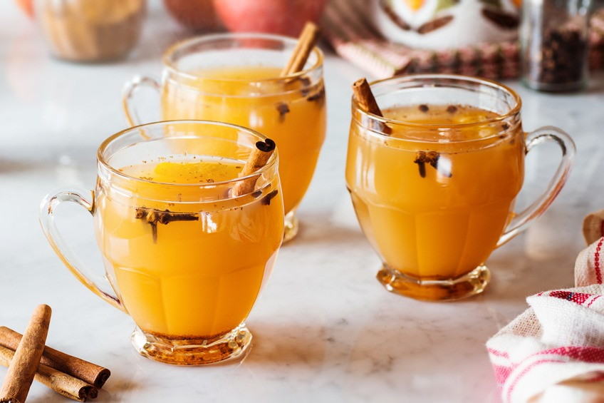 Three glass mugs of steaming hot mulled apple cider