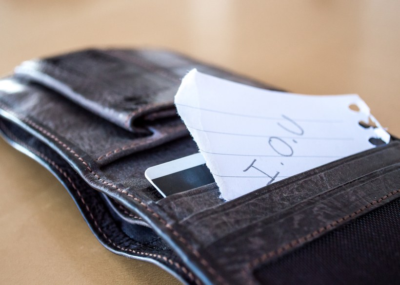 An 'I.O.U' message on a piece of paper, sticking out of a leather wallet