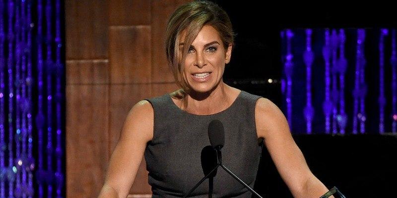 Jillian Michaels is talking at a podium in a dress.