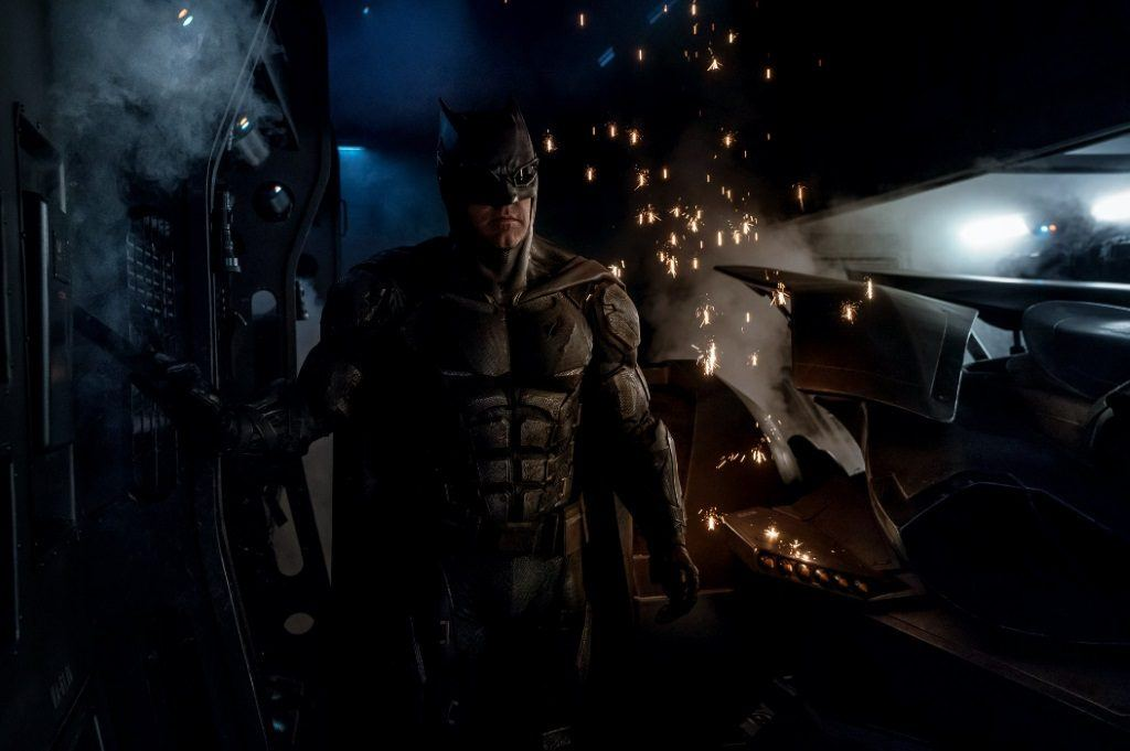 """Batman wearing """"Tactical Batsuit"""" in Justice League with sparks and steam behind him"""