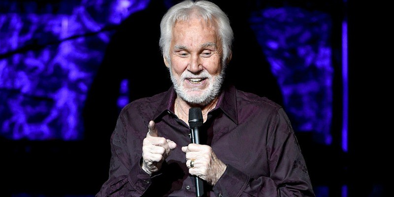 Kenny Rogers is speaking on stage holding a microphone.