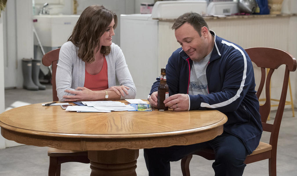 Kevin James sits at a table with a beer next to woman in a scene from Kevin Can Wait