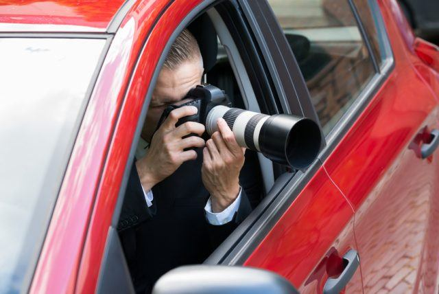A photographer takes pictures out of the window of his car