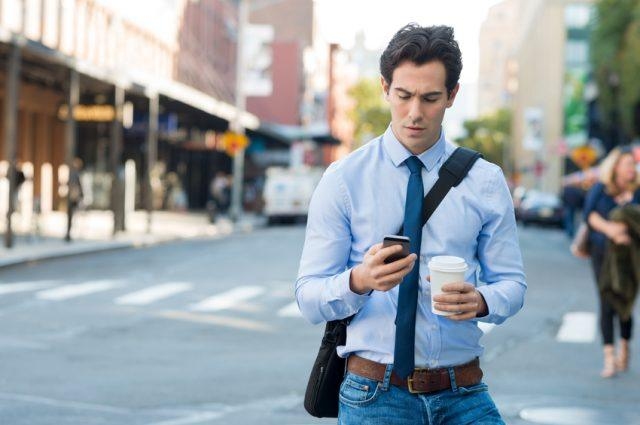 Businessman texting on smartphone and holding paper cup