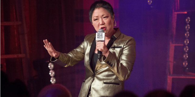 Margaret Cho performs while holding a microphone on stage.