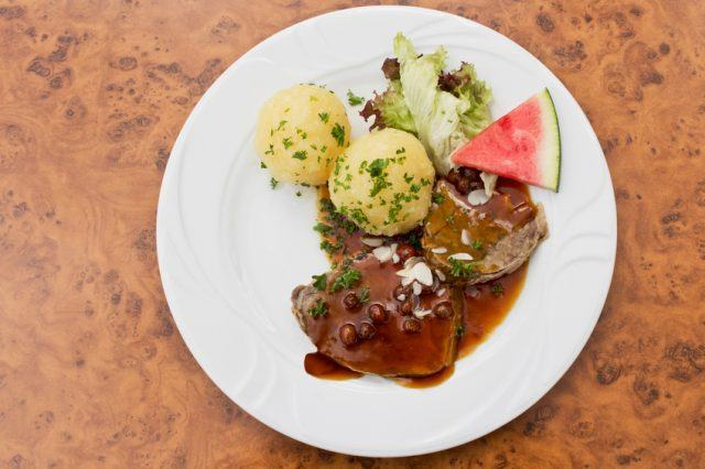 Marinated beef on a plate with potatoes, lettuce, and watermelon