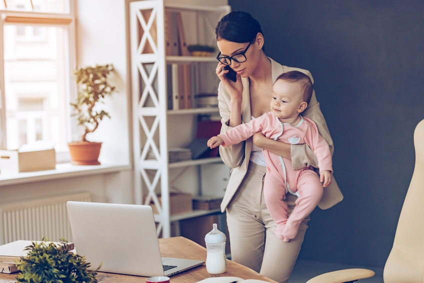 beautiful businesswoman talking on mobile phone while standing with her baby girl