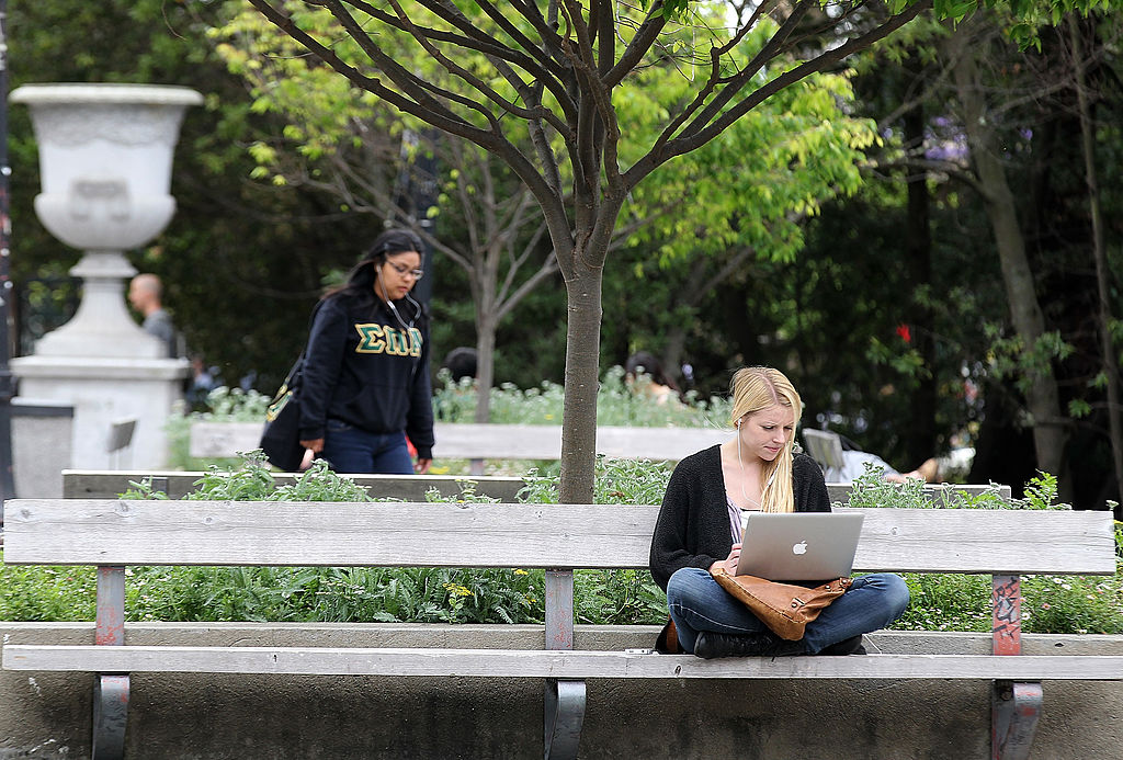 A UC Berkeley student works on her laptop while sitting on a park bench at the UC Berkeley campus