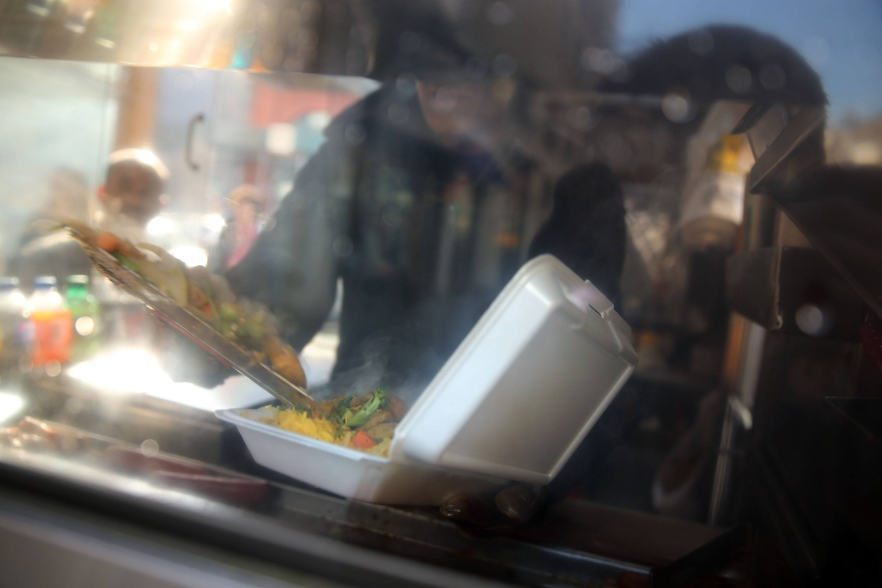 A food cart worker fills a styrofoam take-out container with food