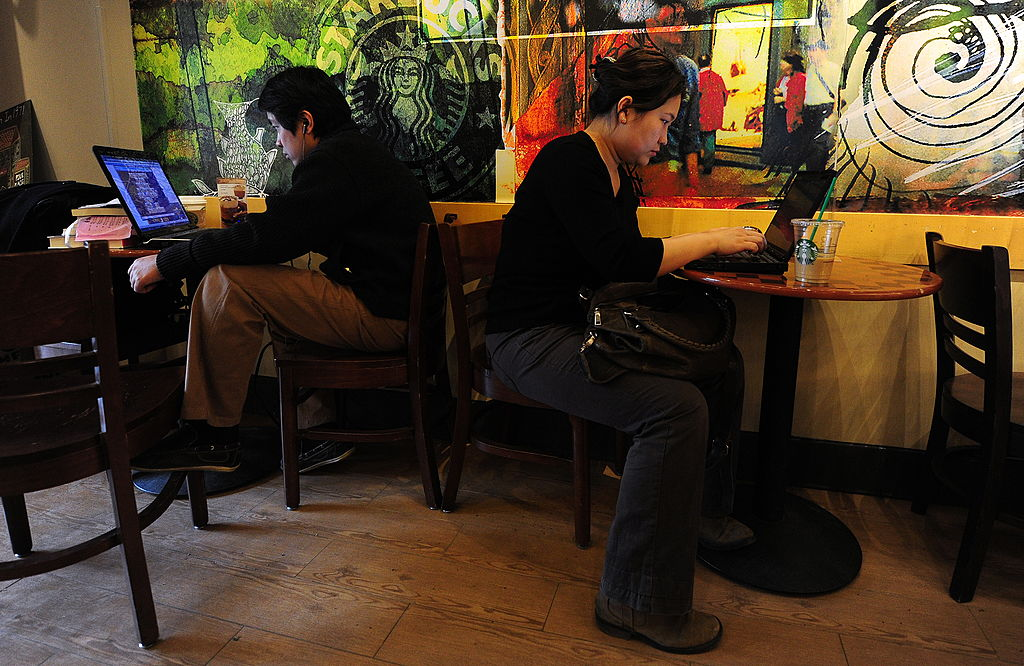 People use their laptop computers at a cafe in Beijing