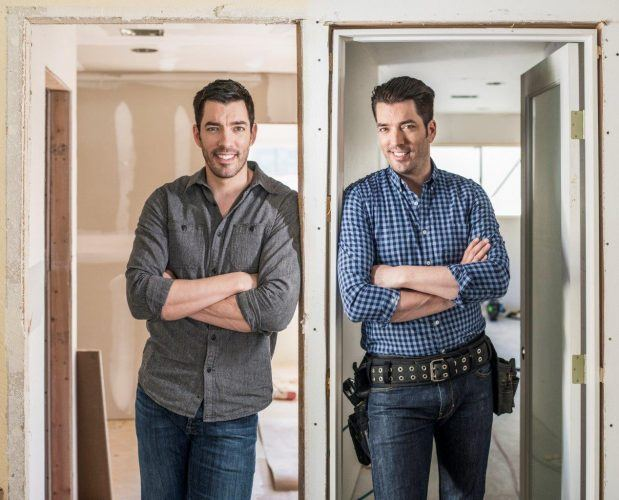 Jonathan and Drew Scott stand together in a renovated house.