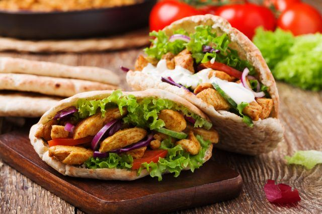 A pita sandwich filled with vegetables and chicken.