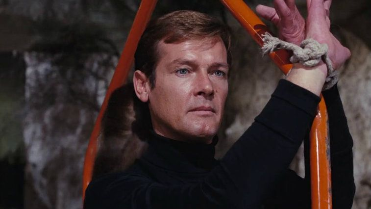 Roger Moore stares ahead as his hands are tied to a metal bar in Live and Let Die