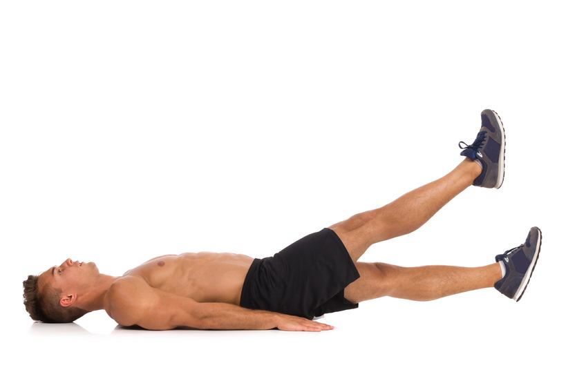 Muscular man lying on a floor and does a scissors stomach exercise