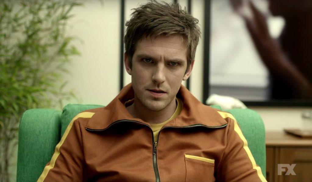 Dan Stevens in an orange jacket, sitting in a chair