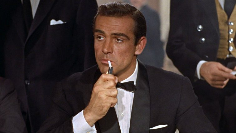 Sean Connery as James Bond, casually lighting a cigarette