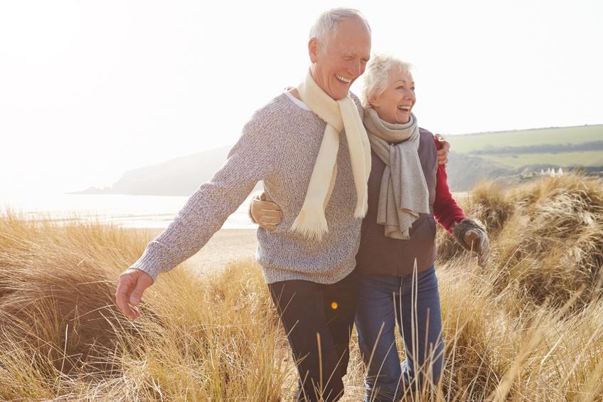 senior couple walking on sand