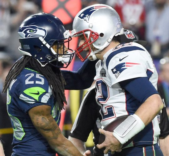 New England Patriots quarterback Tom Brady(R) is congratulated by Richard Sherman